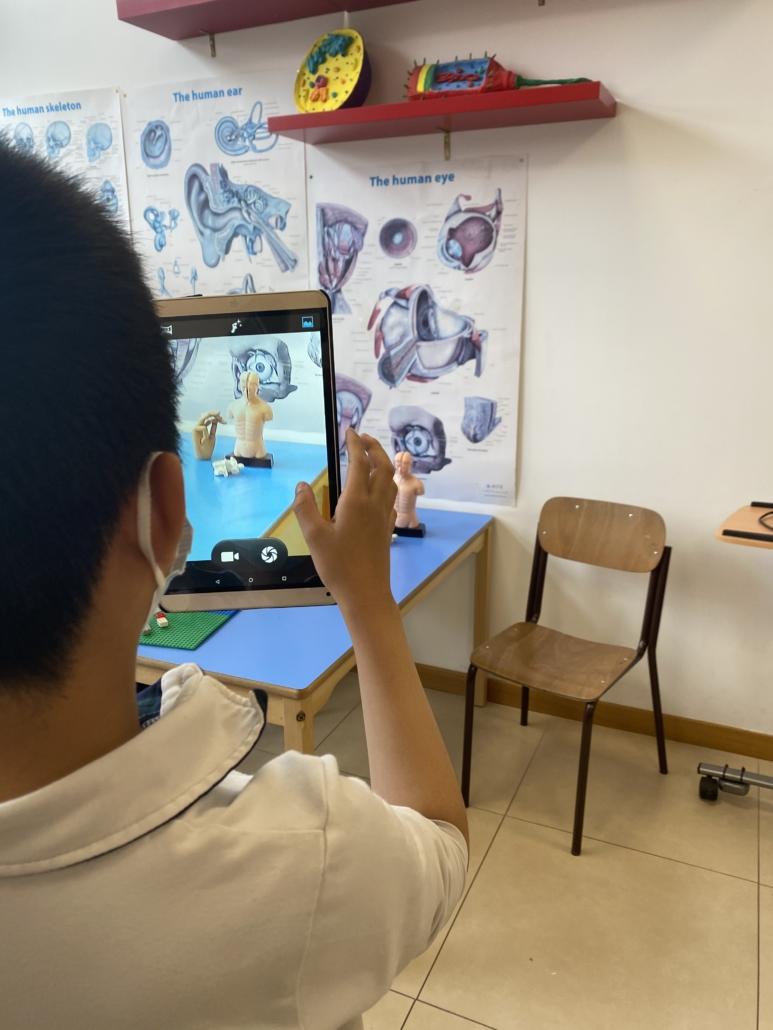 Studente che fotografa un modellino di corpo umano.